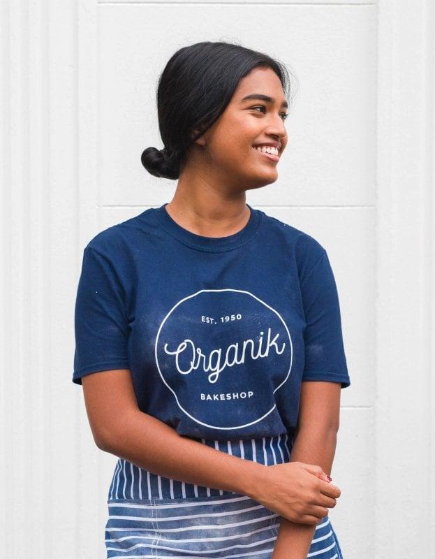Foto av kvinna som bär en t-shirt med logotyp för Organik Bakeshop