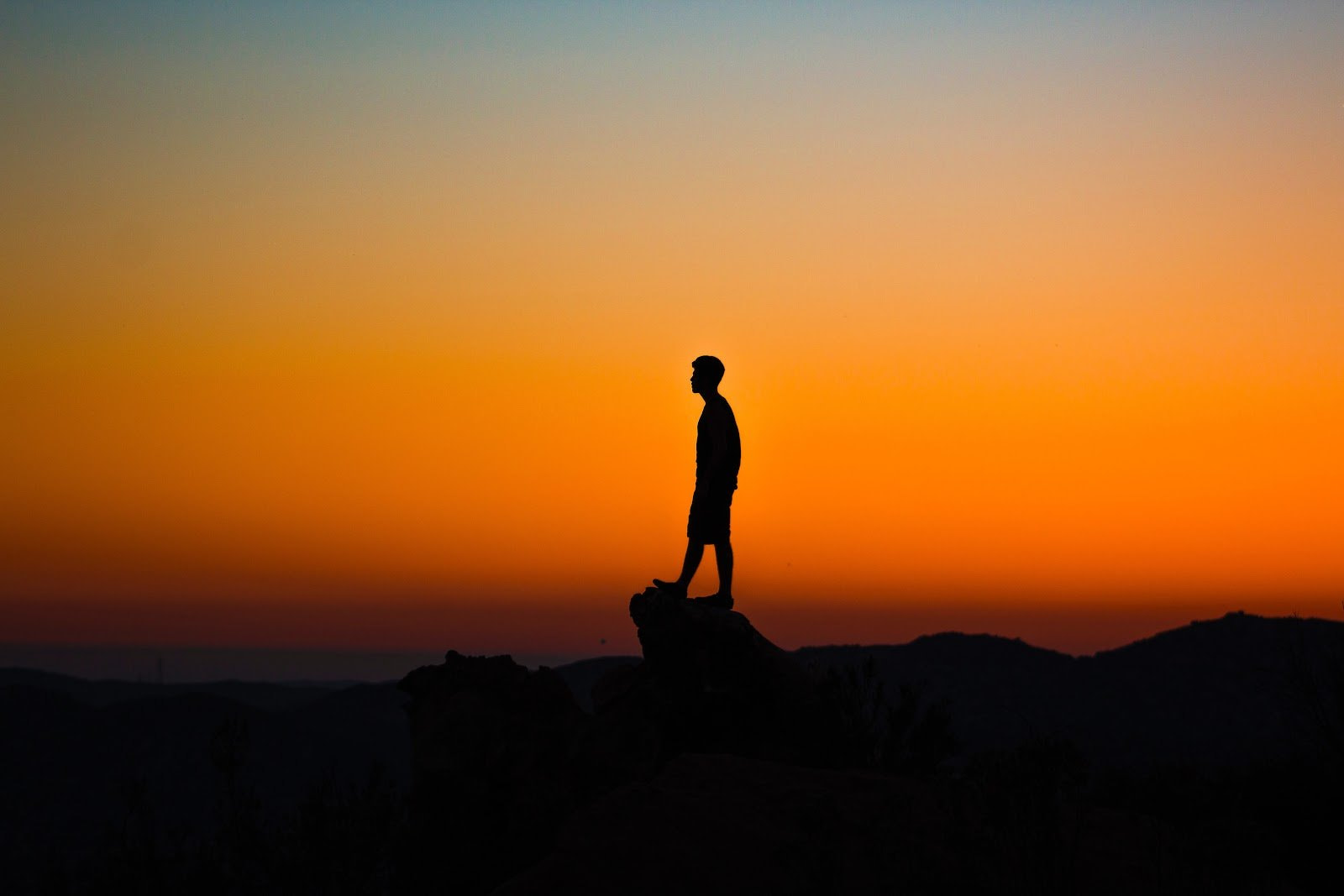 Silhouette of a man standing on a cliff by Austin Mabe