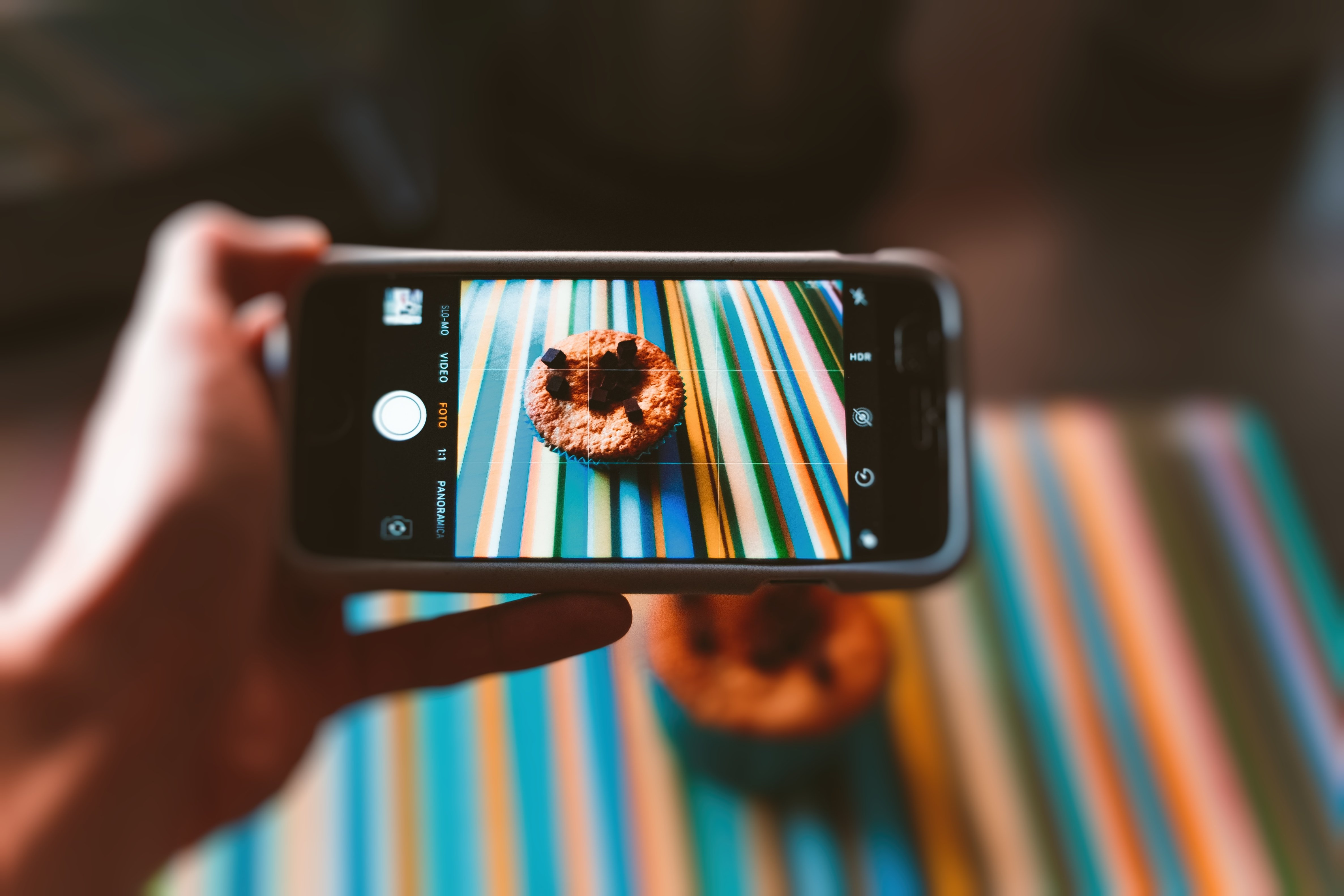 Close-up of hand using mobile phone while photographing muffin