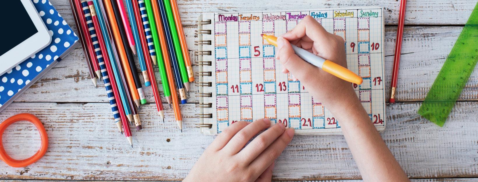 Kind am Holztisch einen Stundenplan malend, umgeben von Stiften, Büchern, Tablet, Lineal und mehr.