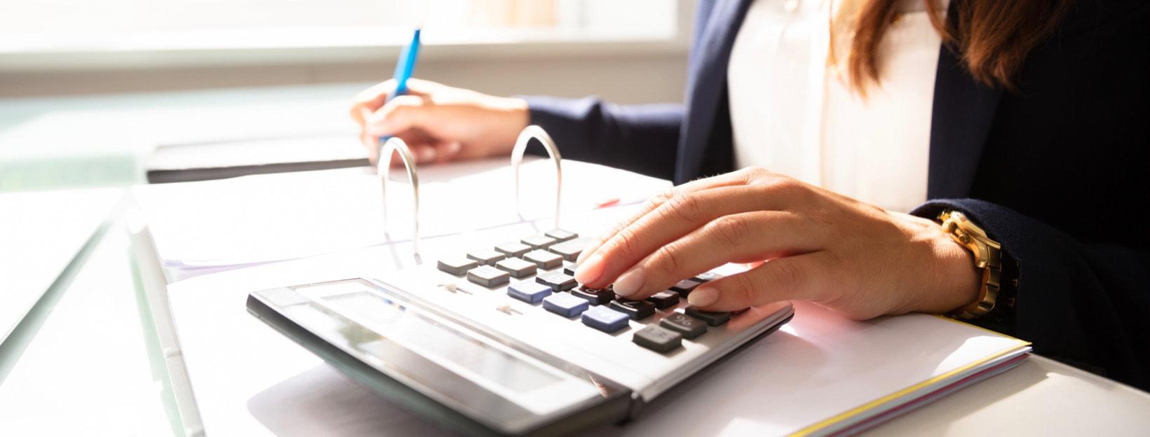 Geschäftsfrau mit Taschenrechner und Rechnungen