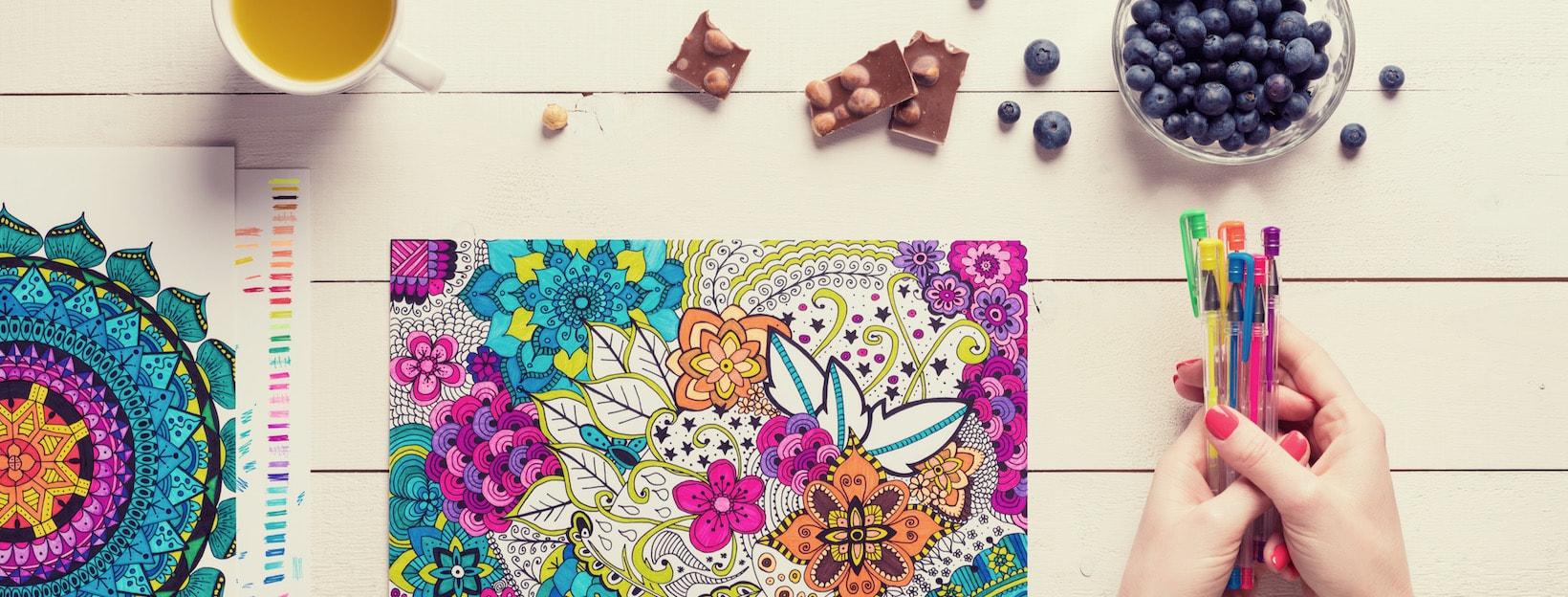 Buntes Ausmalbild mit Stiften, Tee und Snacks