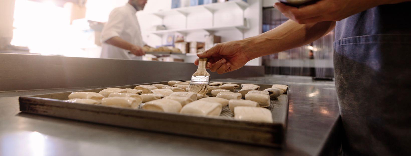Baker with brush prepares rolls for baking