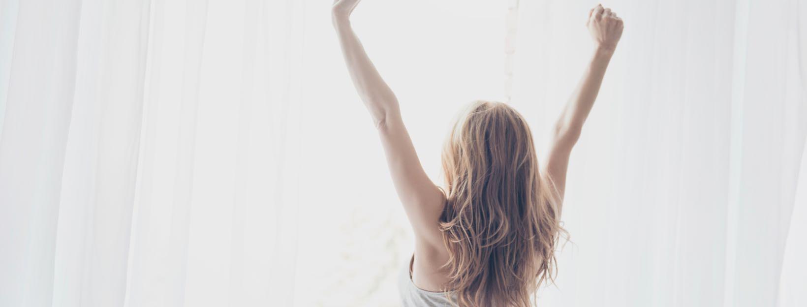 Frau streckt sich motiviert vorm Fenster