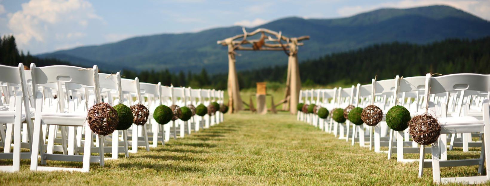 Hochzeit planen: Hochzeitszeremonie im Freien mit Stühlen und Bergkulisse