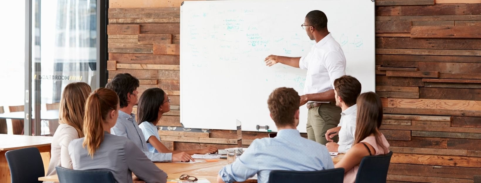 BANNER-Canva-MACXVYoITDY-young-black-man-at-whiteboard-giving-a-business-presentation