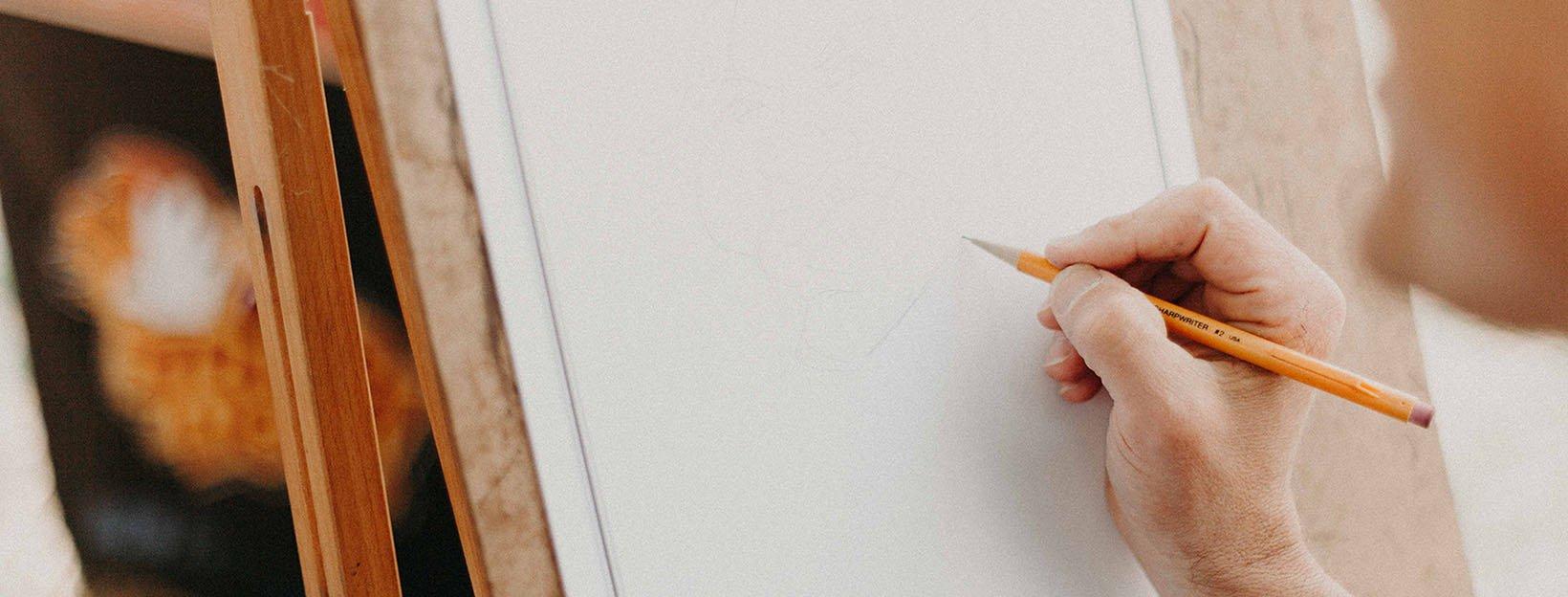 Gestaltungsprinzipien im Design: Hand mit Bleistift vor leerem Blatt