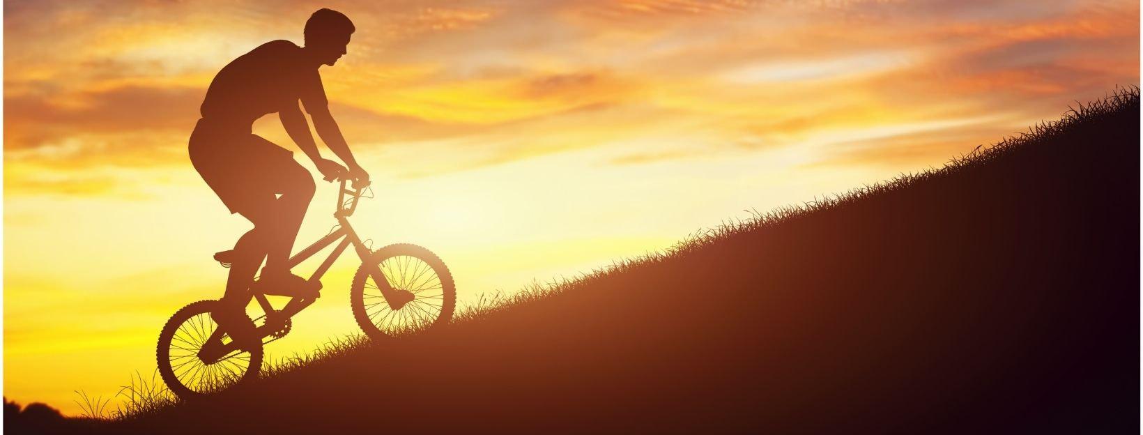 BANNER-Canva-MADatBDrSFc-man-riding-a-bmx-bike-uphill-against-sunset-sky-strength-challenge-2
