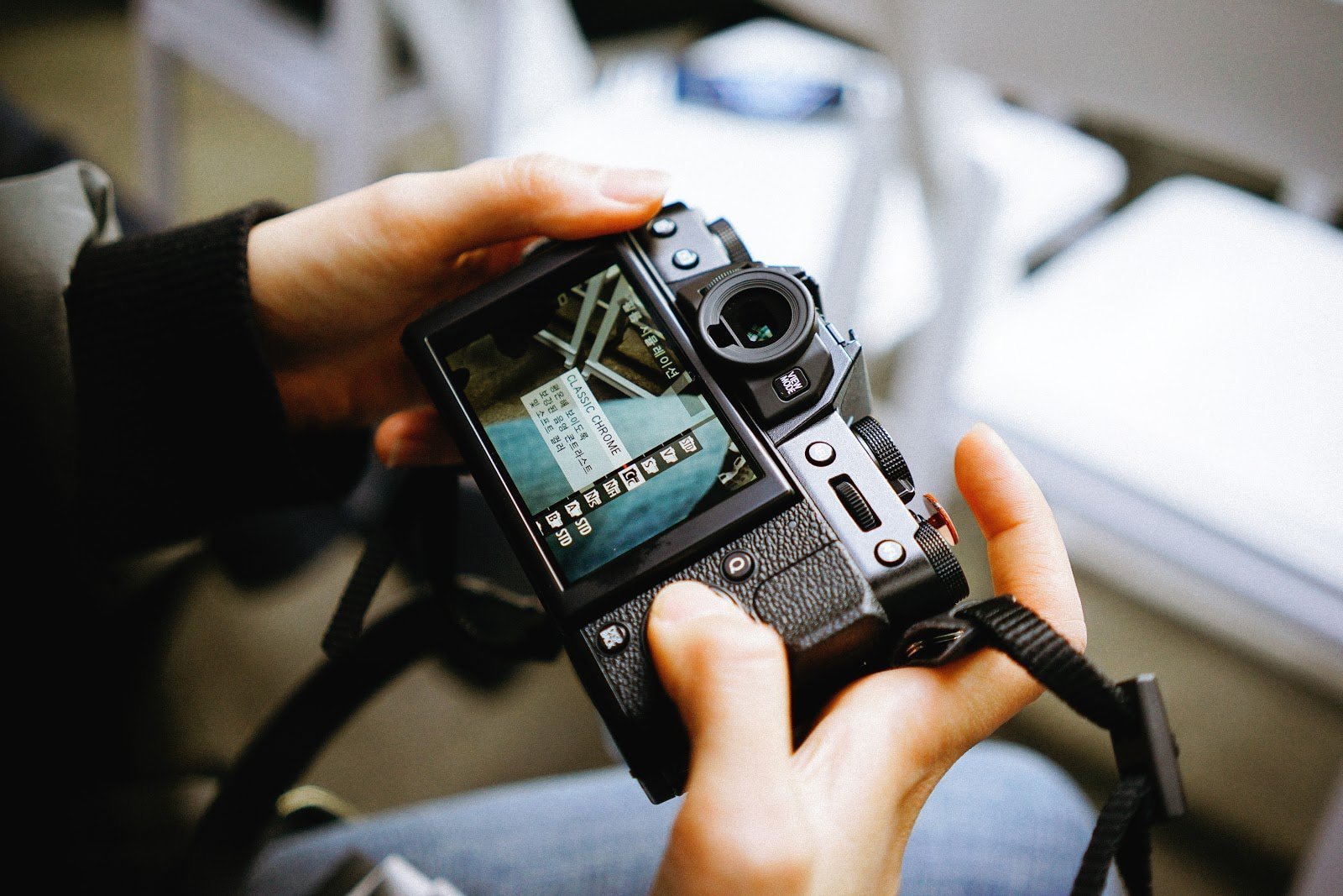 Person holding a camera adjusting its settings by Manki Kim