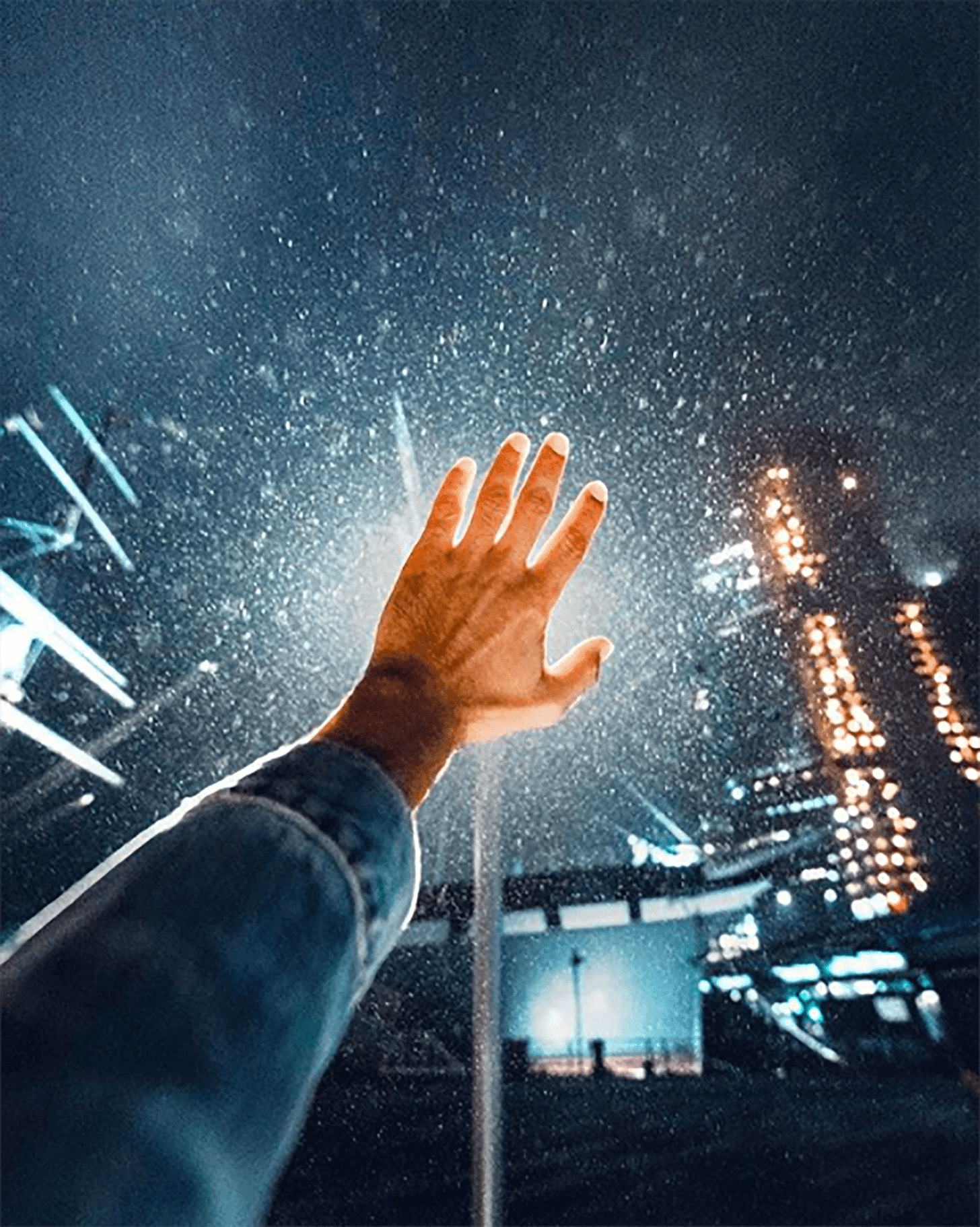 A hand rising up against the falling rain by Ravi Vora