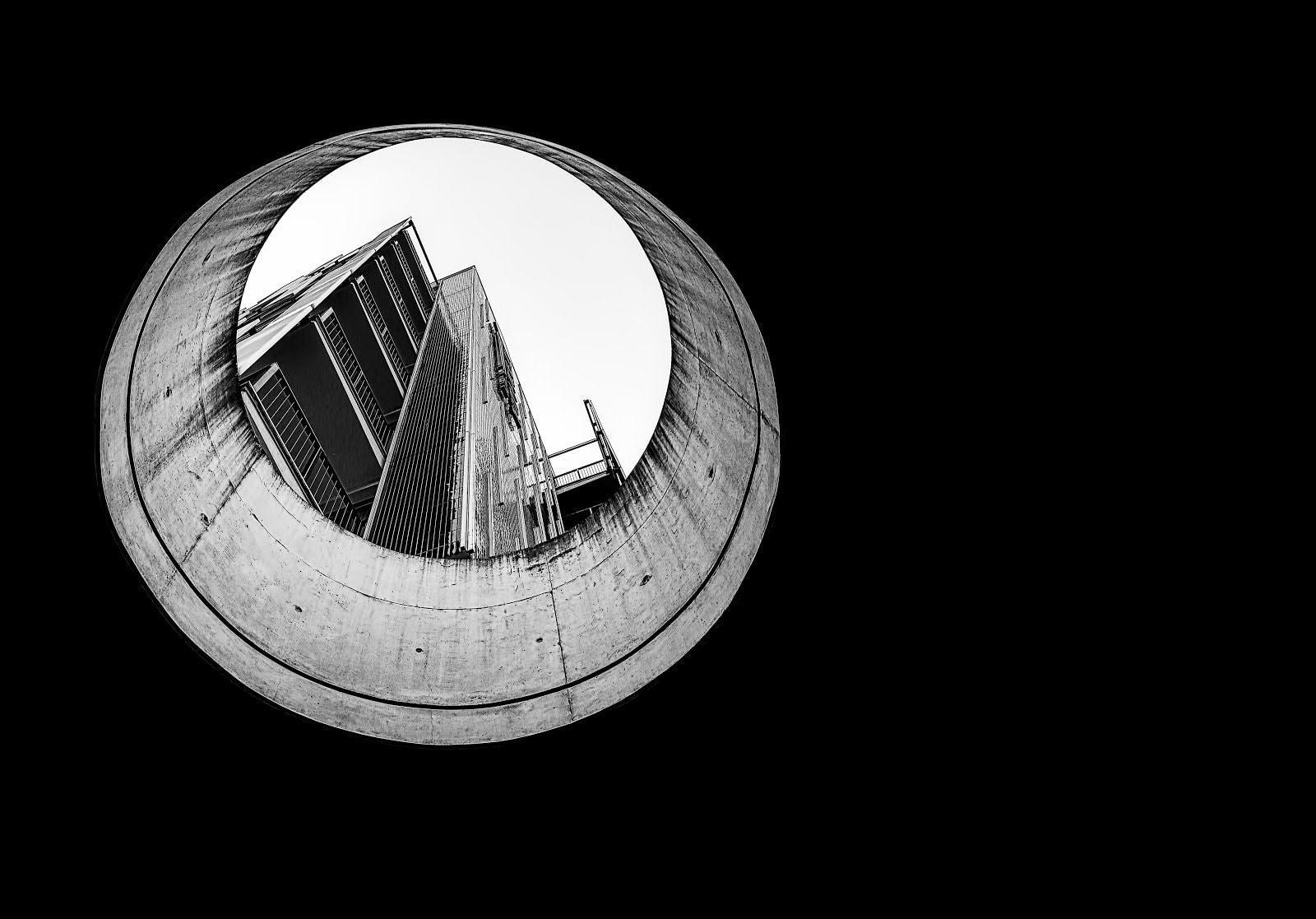 Monochrome photo of a building seen through a hole by Ricardo Gomez Angel
