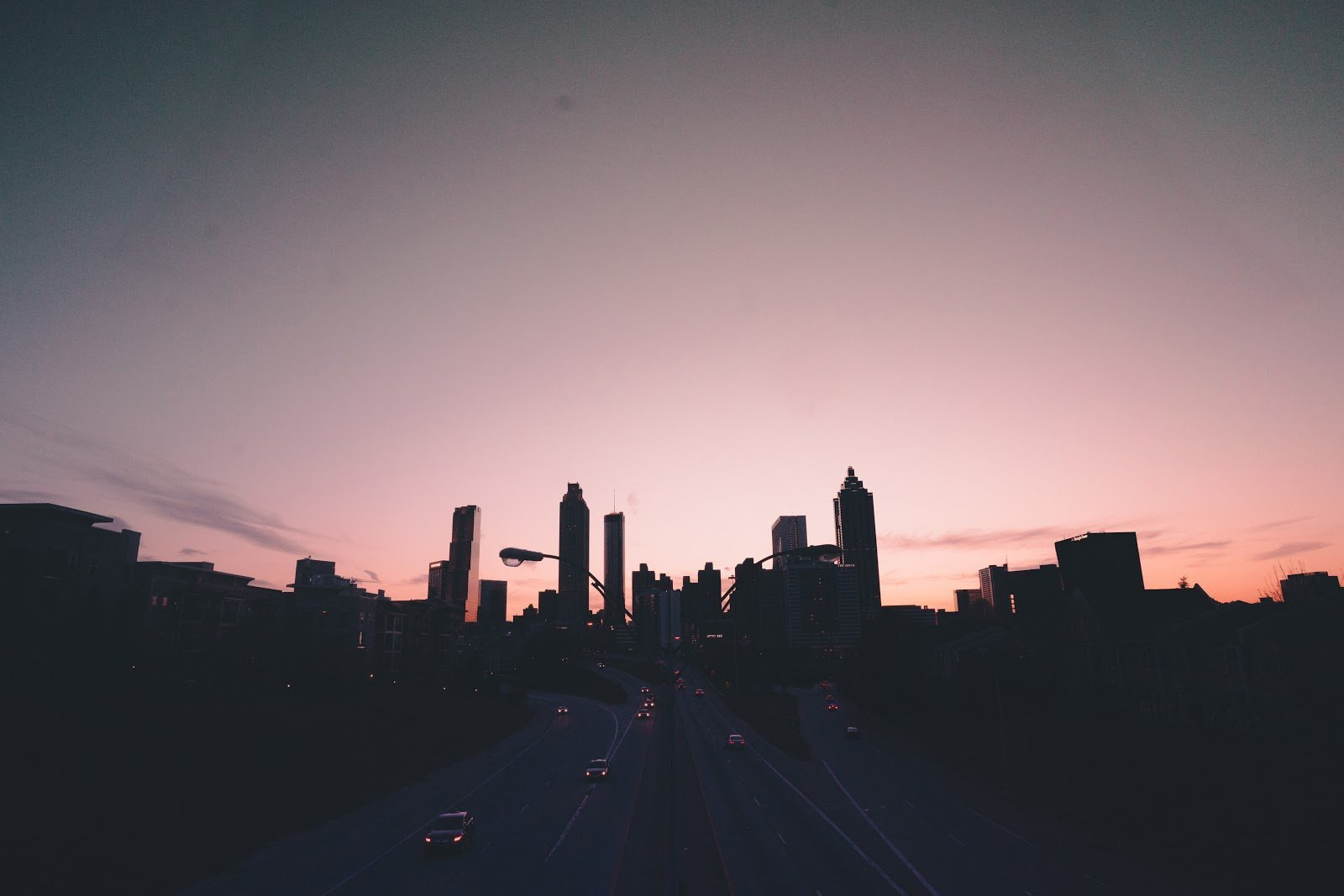 Silhouette of a city skyline and a road by Joe Yates