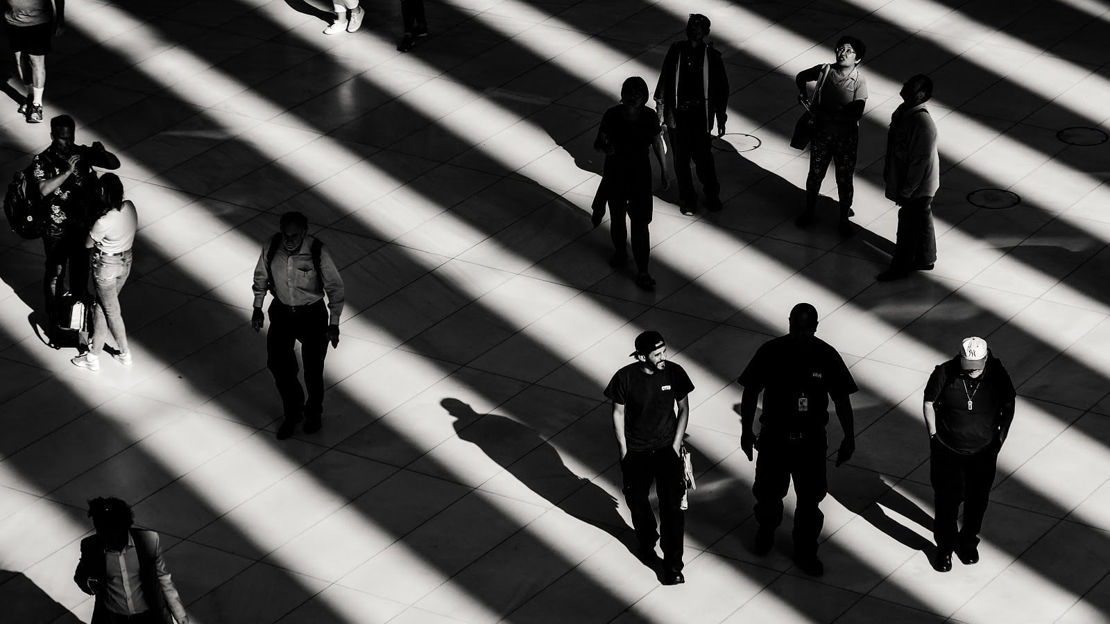 Monochromatic photo of people walking under vertical shadows  Zac Ong
