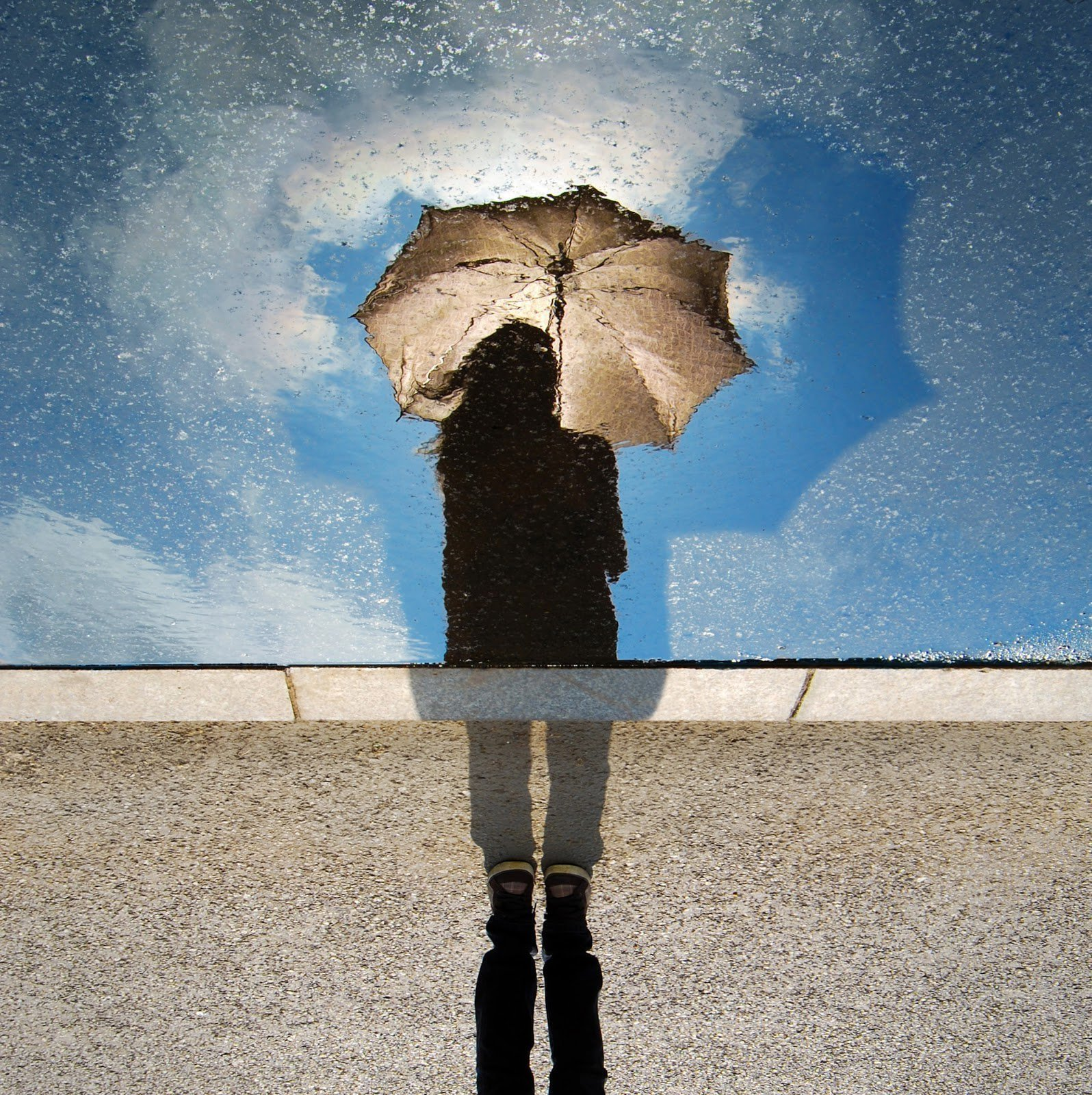 Reflection of a woman holding an umbrella by David Marcu