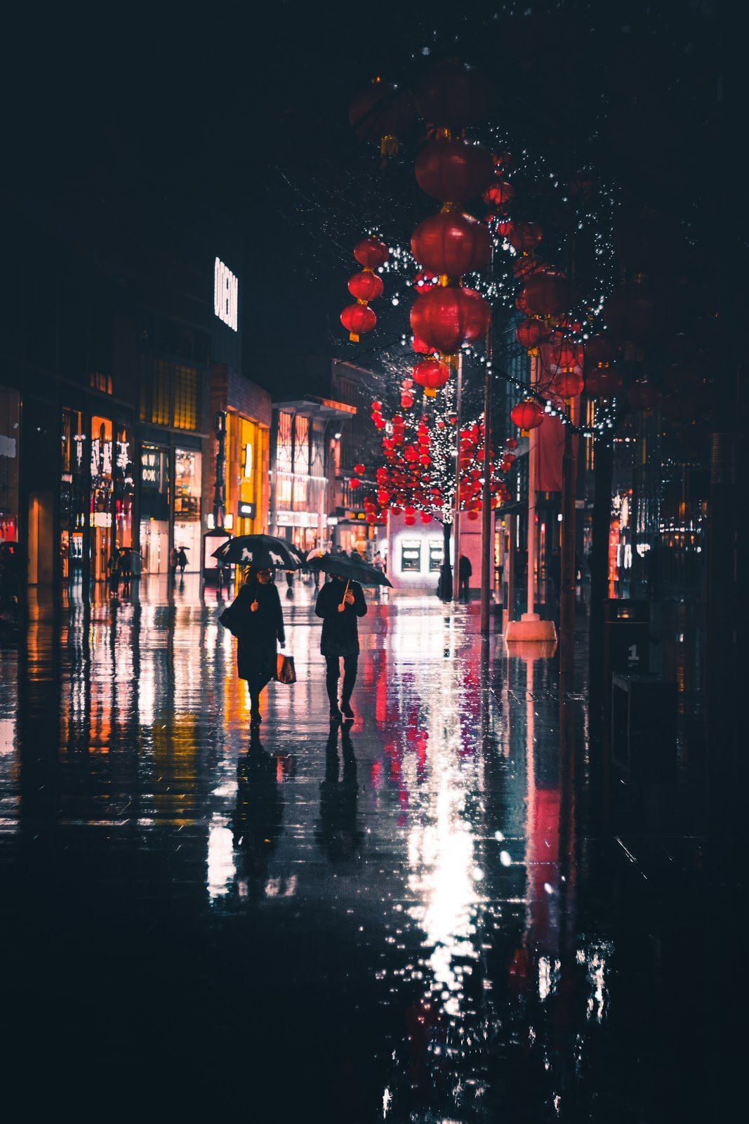 Two people holding umbrellas walking through a rainy street by Jack Finnigan