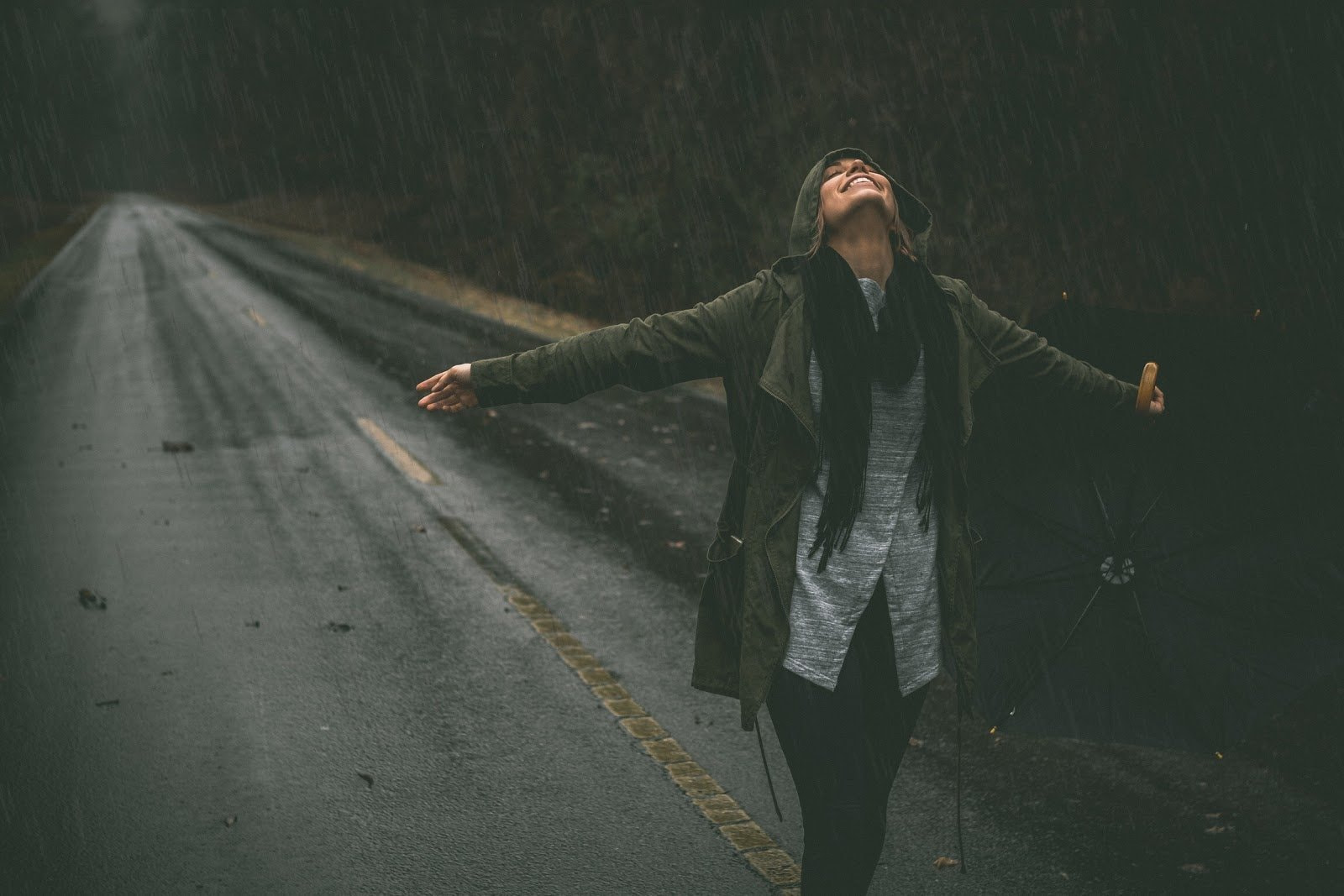 A woman wearing a green coat enjoying the rain by Robb Leahy