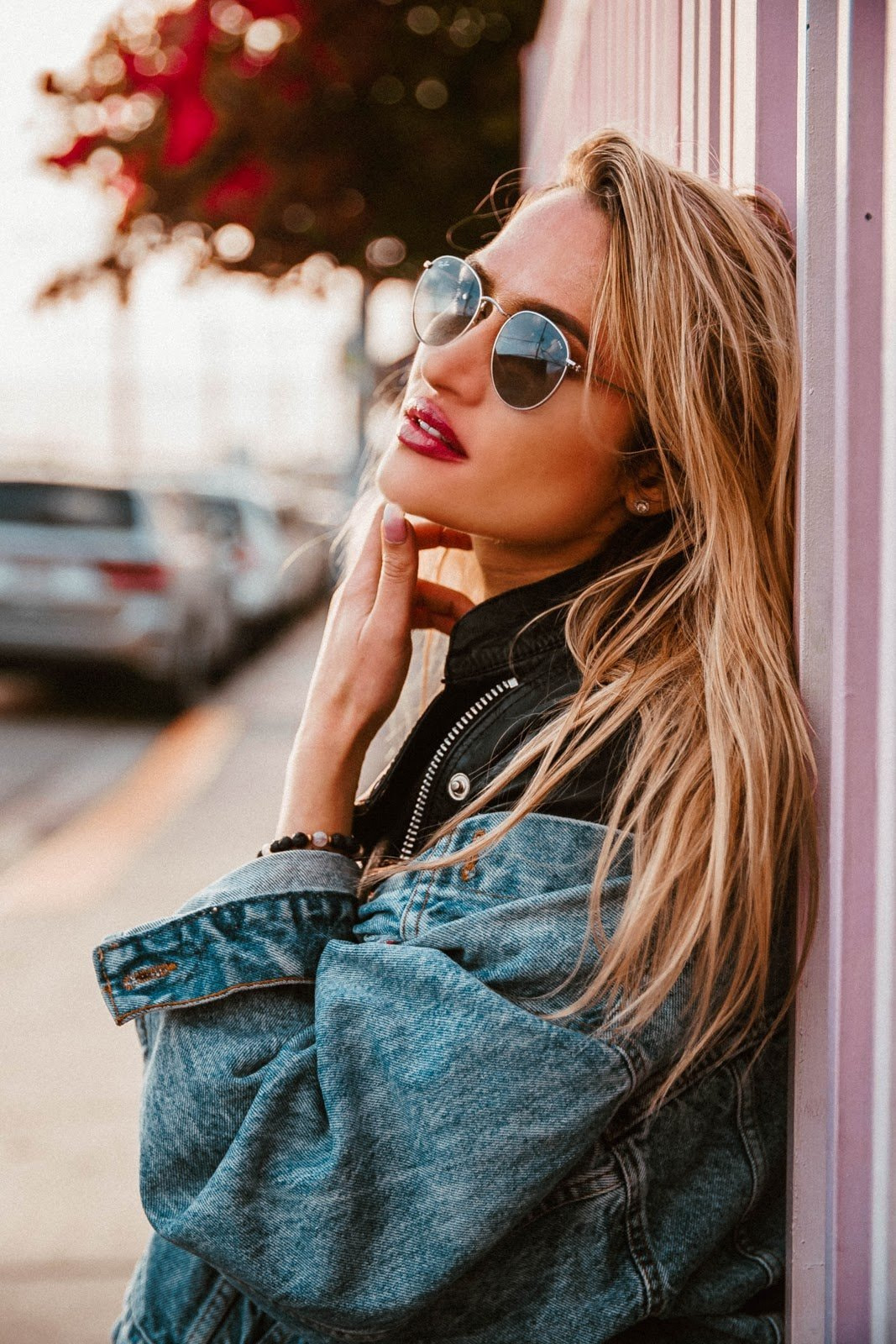 A blonde woman wearing sunglasses and a denim jacket by Frankie Cordobba