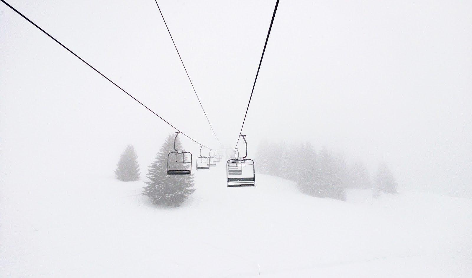Chair lifts on a foggy ski slope by Geoffrey Arduini