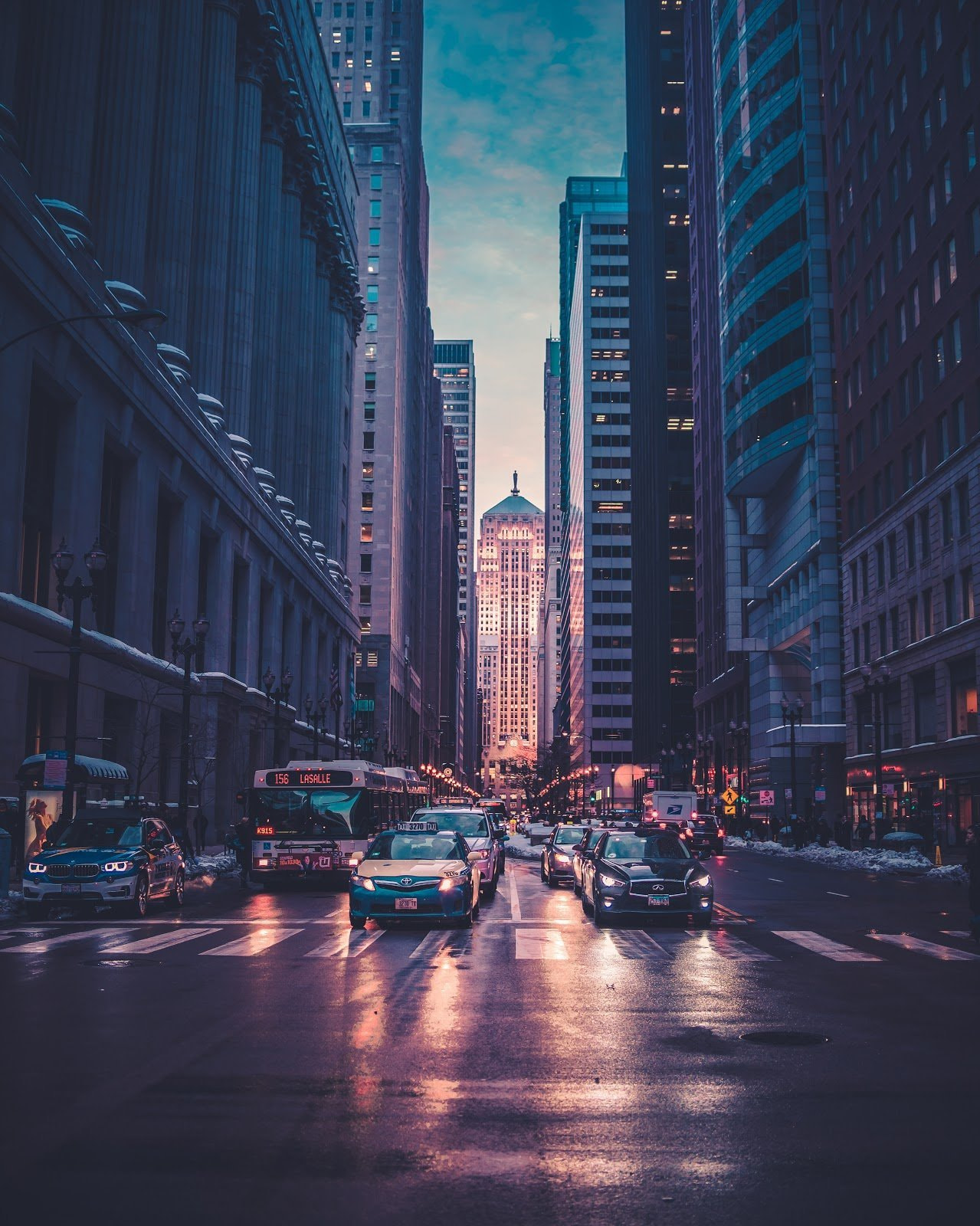 Buildings and a busy city street during the blue hour by Max Bender