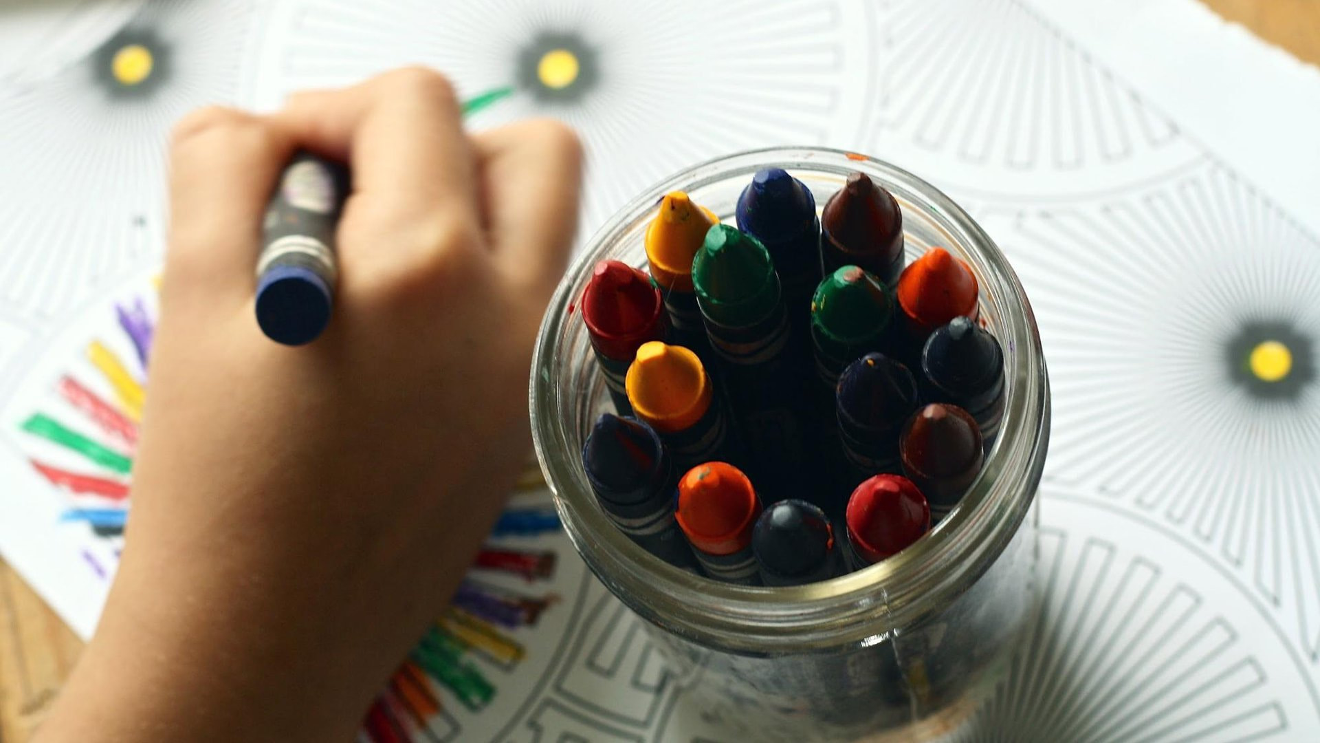 Child coloring an illustration with crayons