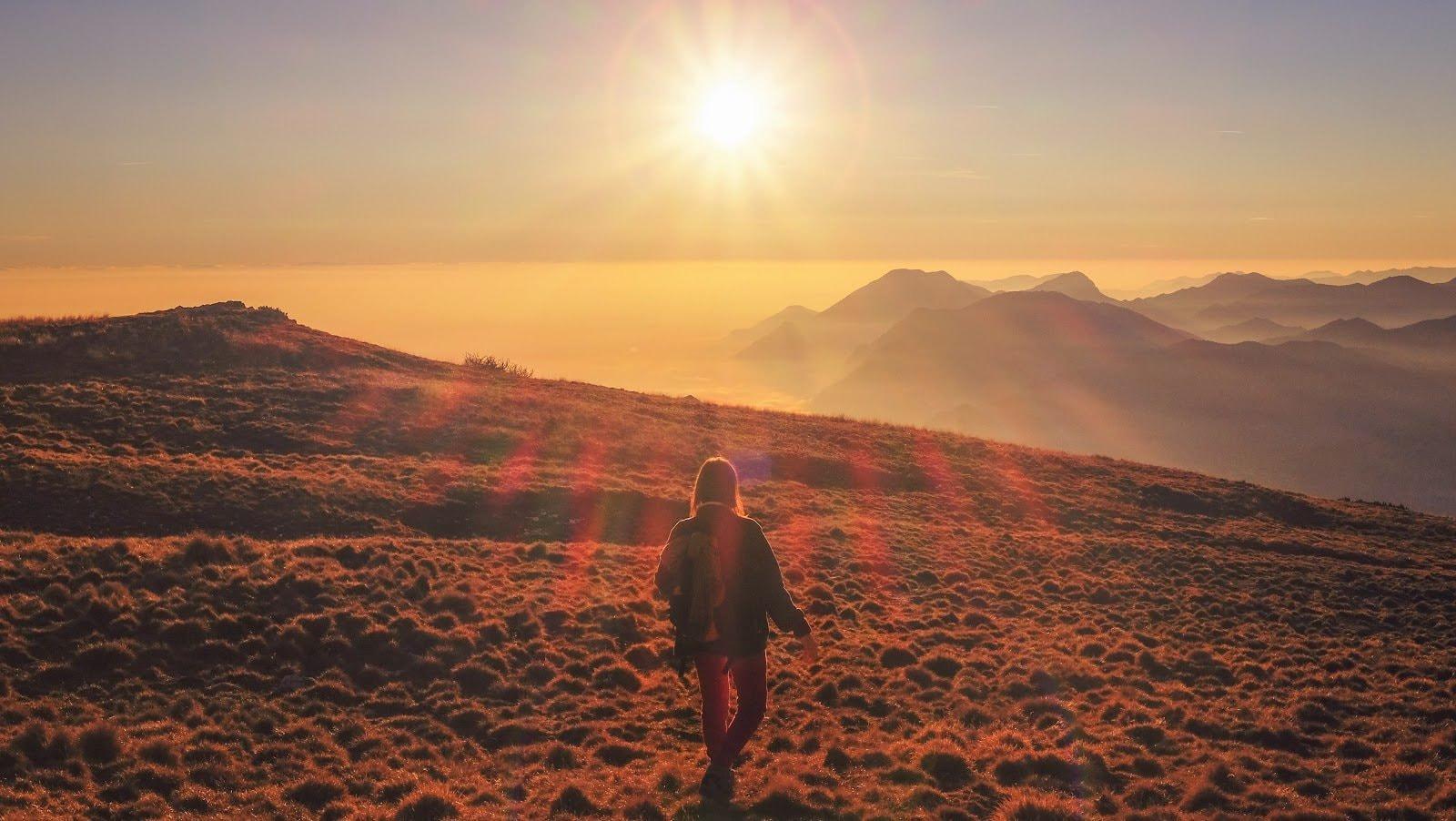 Golden hour photo of a woman walking through a field by Cristina Gottardi