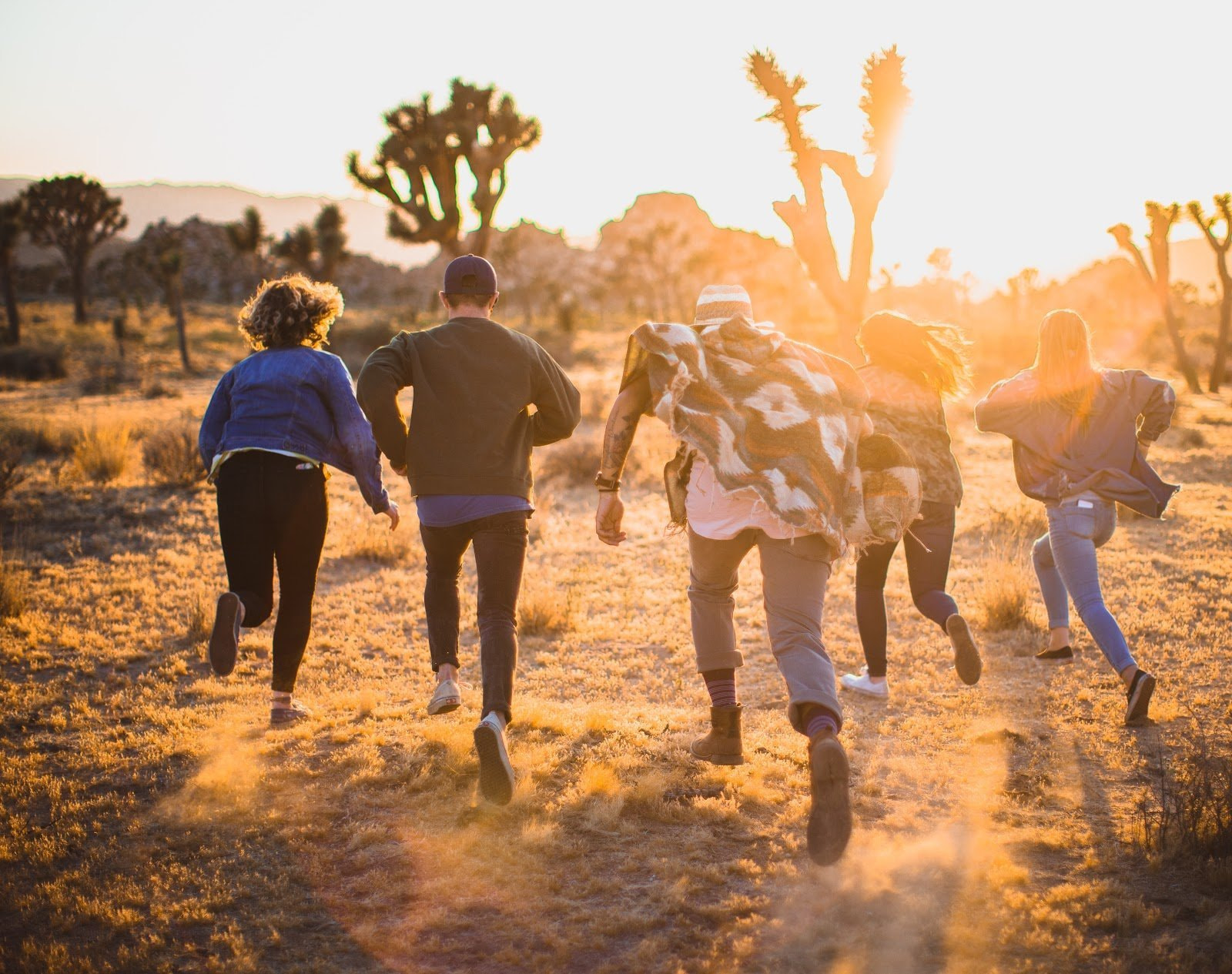 A group of friends running through a field during the golden hour by Jed Villejo