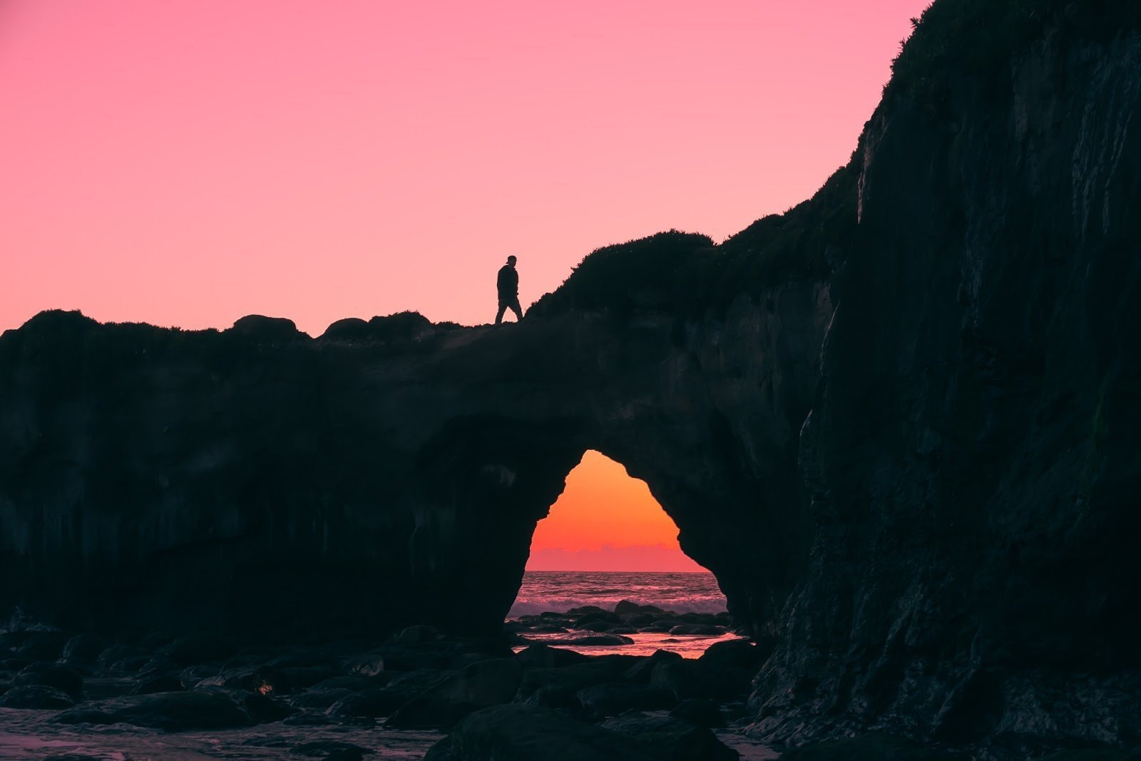 Silhouette of a man walking on a cliff at a beach by Jeff Nissen