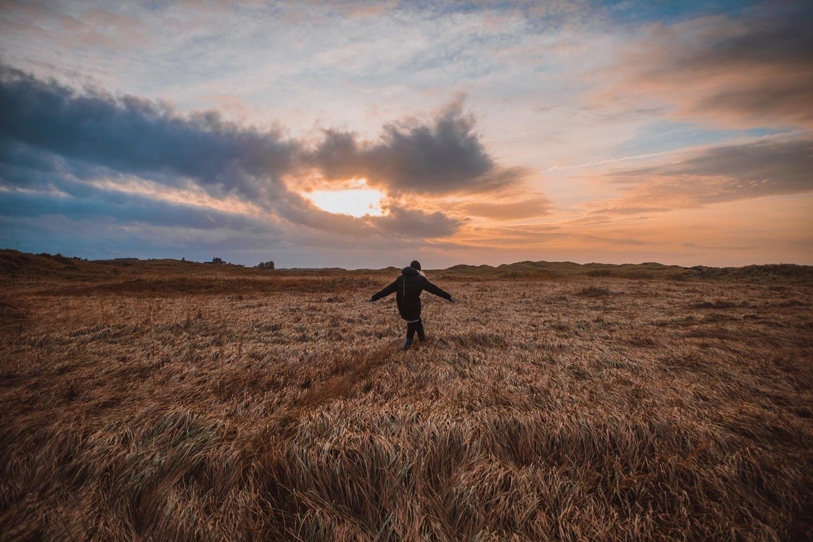 Person walking in a field during the golden hour by Soren Astrup Jorgensen