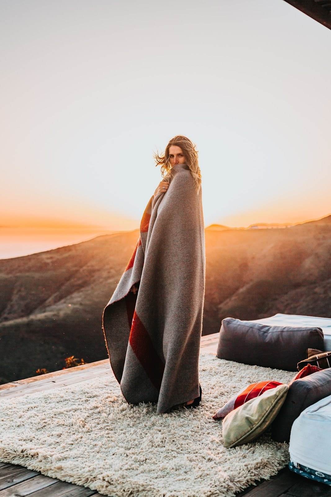Woman wrapped in a blanket during golden hour by Tyler Nix