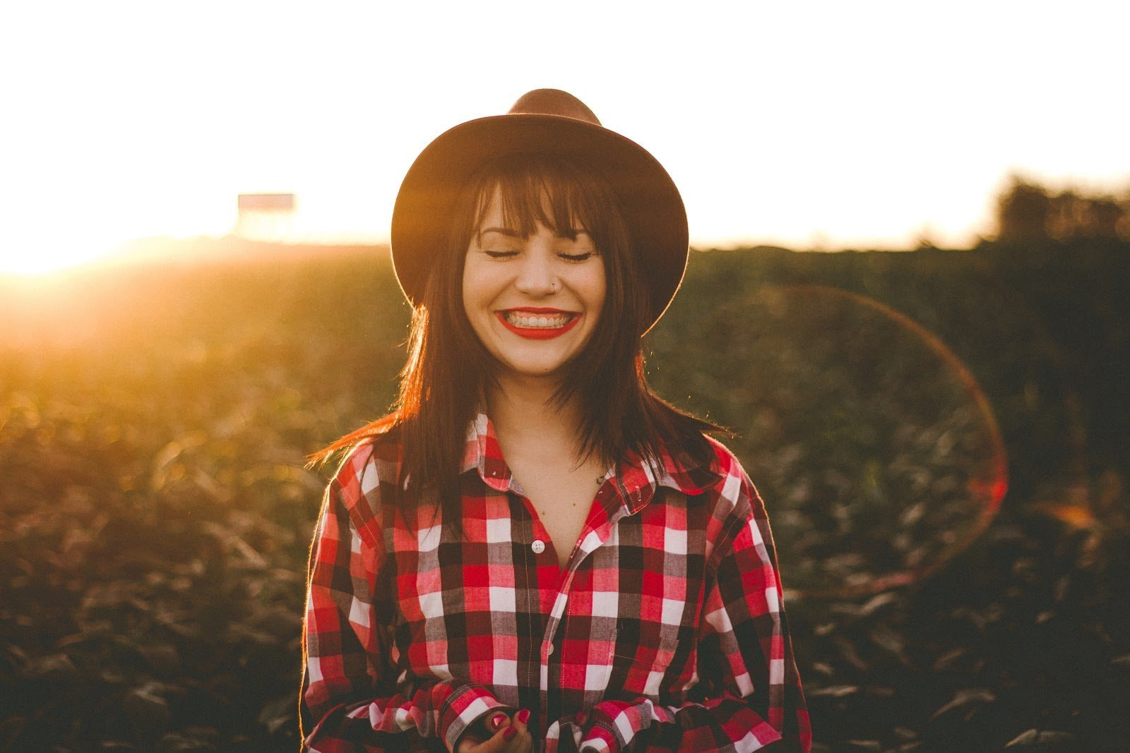 Portrait of a woman smiling with closed eyes during the golden hour by Allef Vinicius