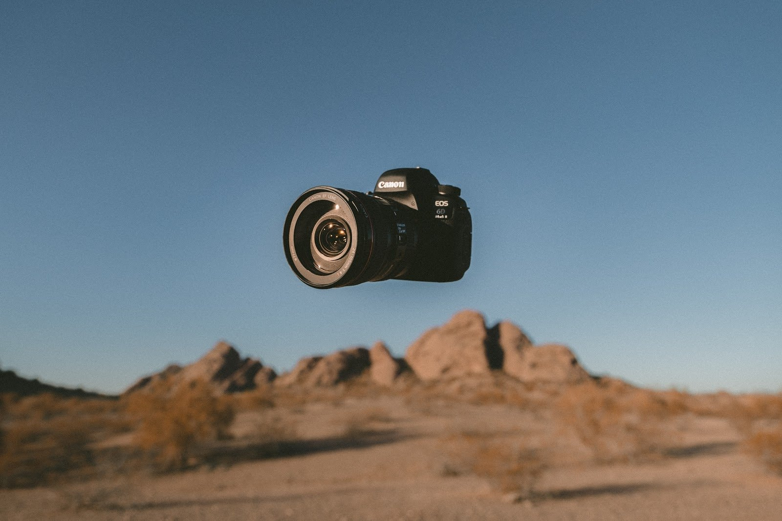 Canon camera floating against a desert backdrop by Jakob Owens