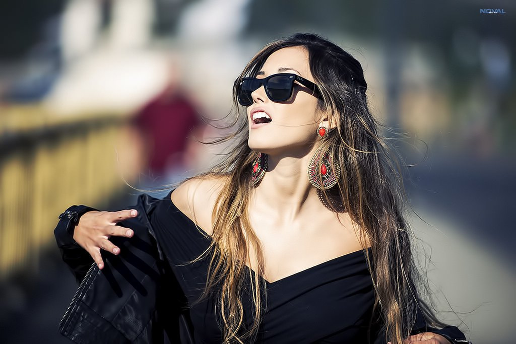 Portrait of a woman with long hair wearing sunglasses by Noval Goya