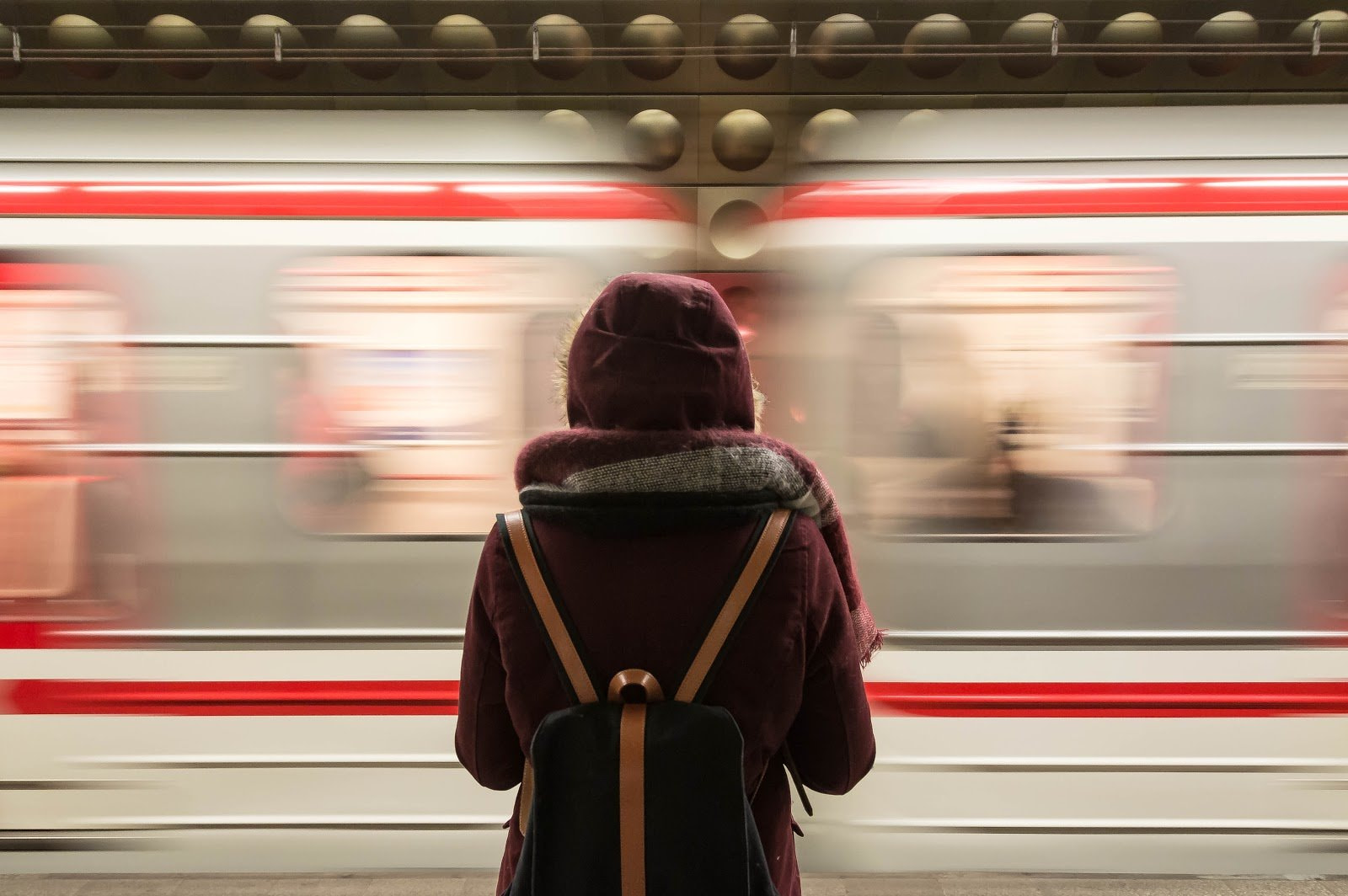 Person in a hoodie with a blurred train passing by by Fabrizio Verrechia