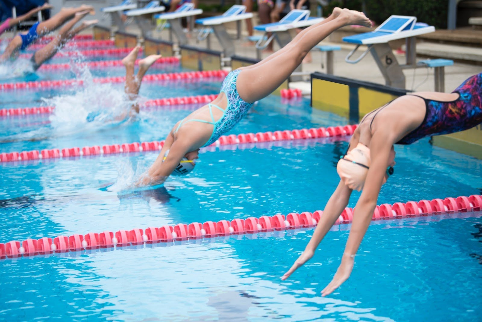 Motion photography of swimmers diving into a pool by Arisa Chattasa