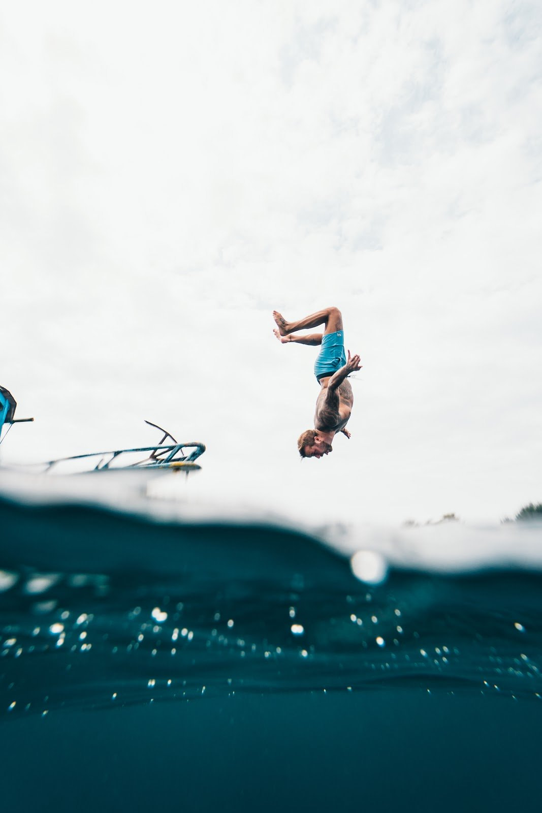 Person doing a backflip from a boat into the ocean motion photography by Oliver Sjöström