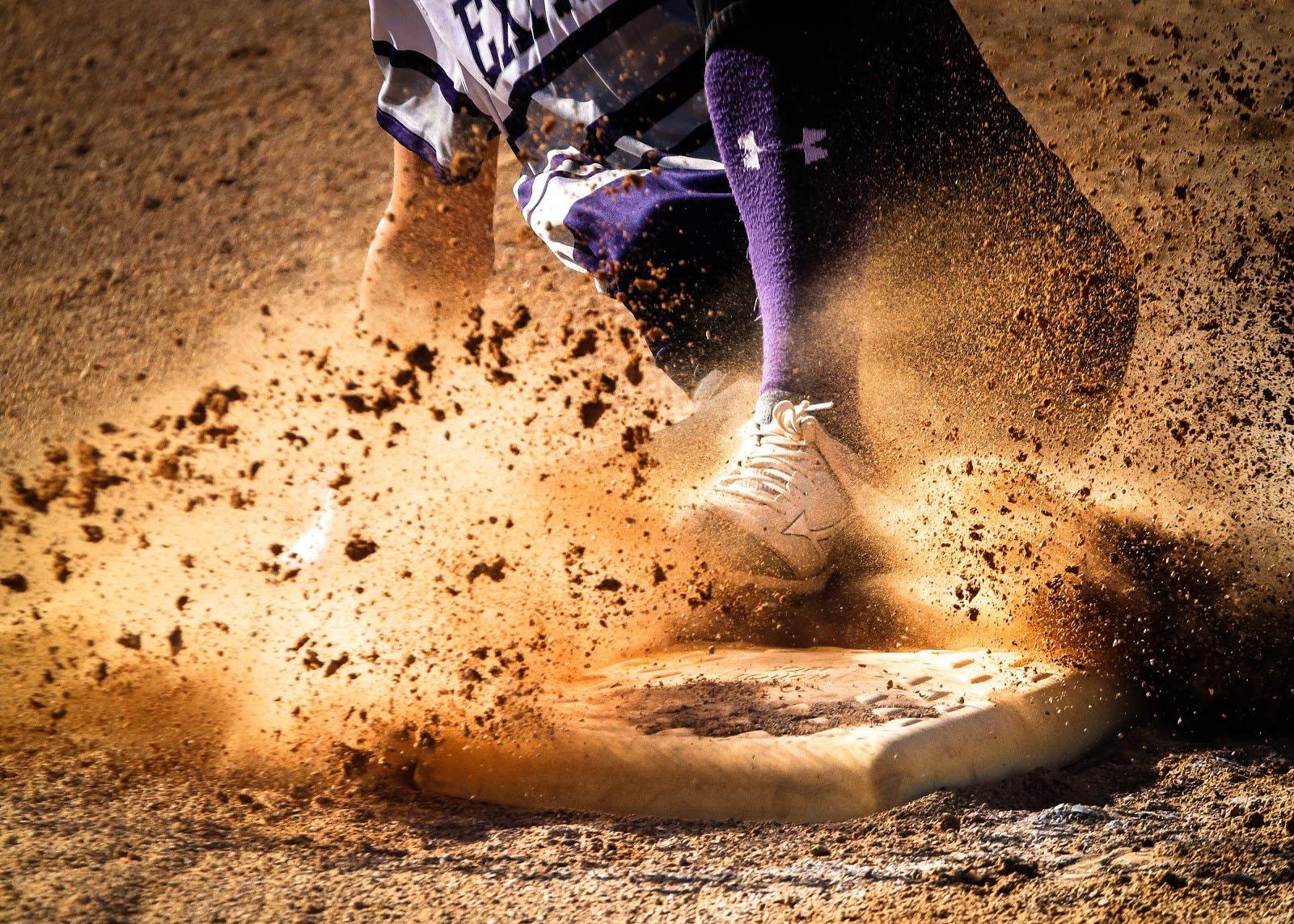 Closeup shot of a baseball player sliding into base by Brandon Mowinkel
