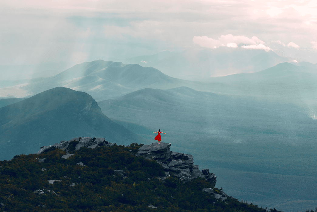Woman on top of a mountain with an overlooking view photo by Louise Coghill