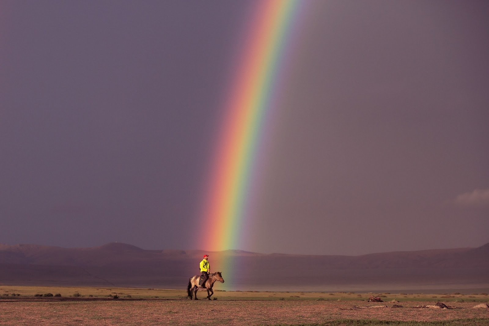 Man riding on a horse on desert with a beautiful rainbow at the back photo by Louise Coghill