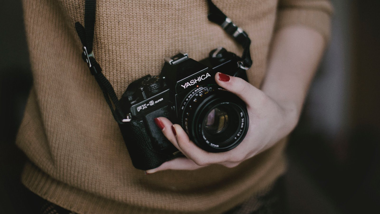 Closeup shot of Yashica camera being held by a woman photo by Mia Domenico