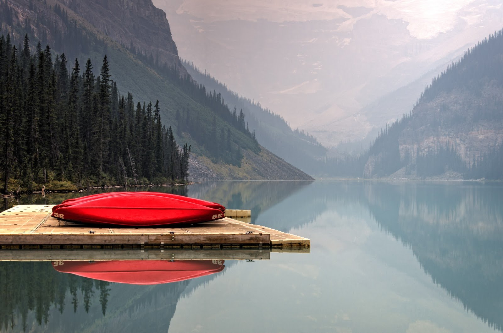 Red boat lying on a dock in in the middle of a mountain view and cold waters photo by Faye Cornish