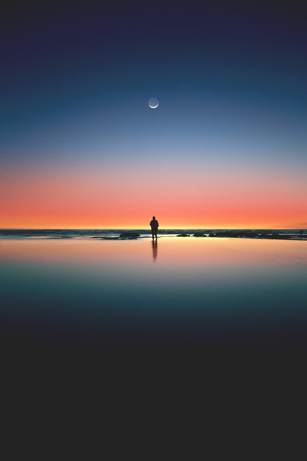 Person standing on a beach using a long exposure shot phot by Jordan Steranka