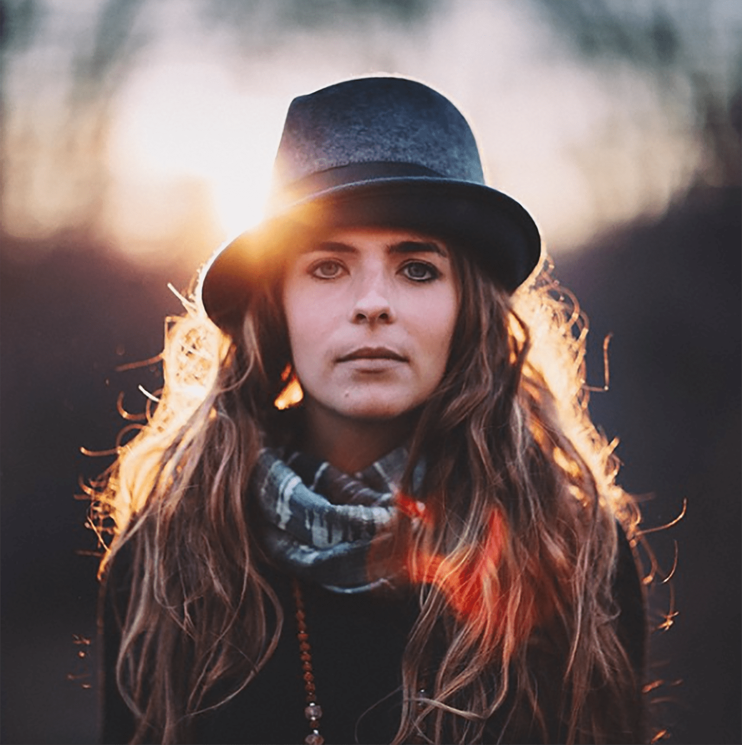 A woman wearing a felt hat and a scarf by Zach Allia
