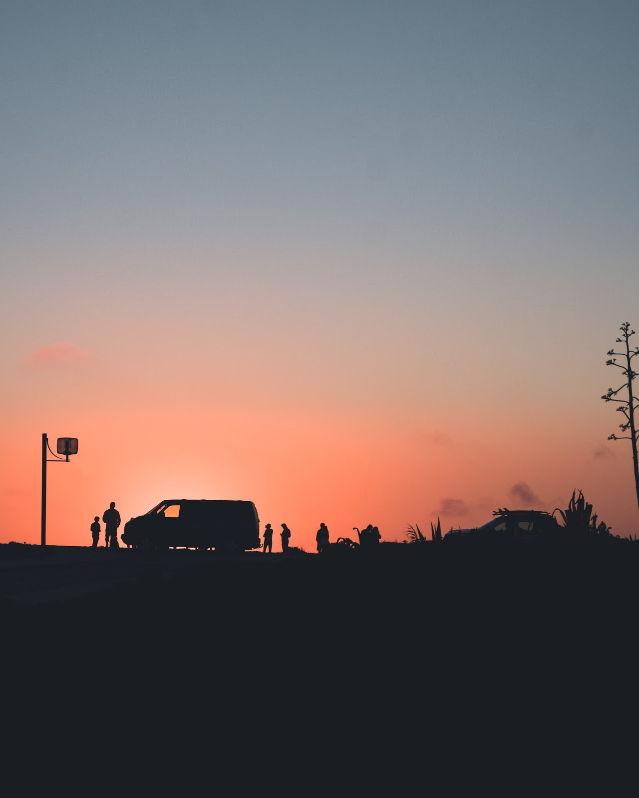 Silhouette of people and a van on a hill during sunset by Diogo Sousa