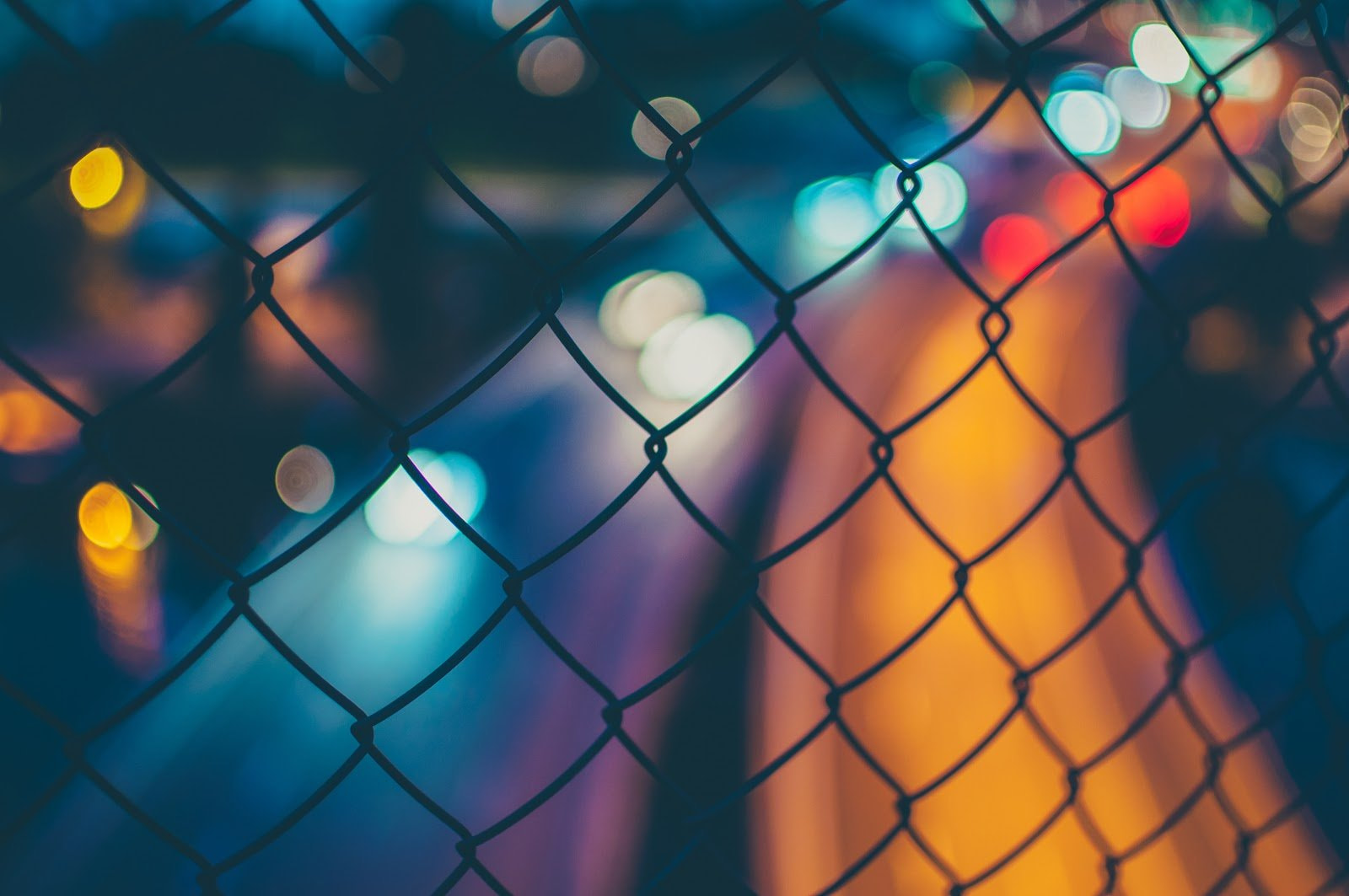Chainlink fence in the foreground with bokeh city lights blurred in the background by Oscar Söderlund