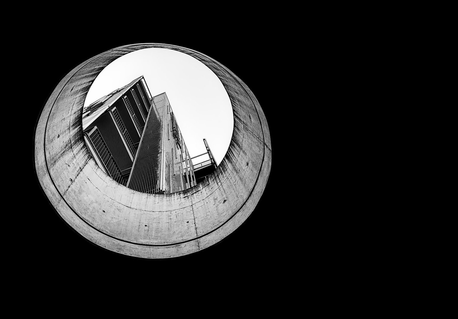 Monochrome photo of a building seen through a hole by Ricardo Gomez Angel