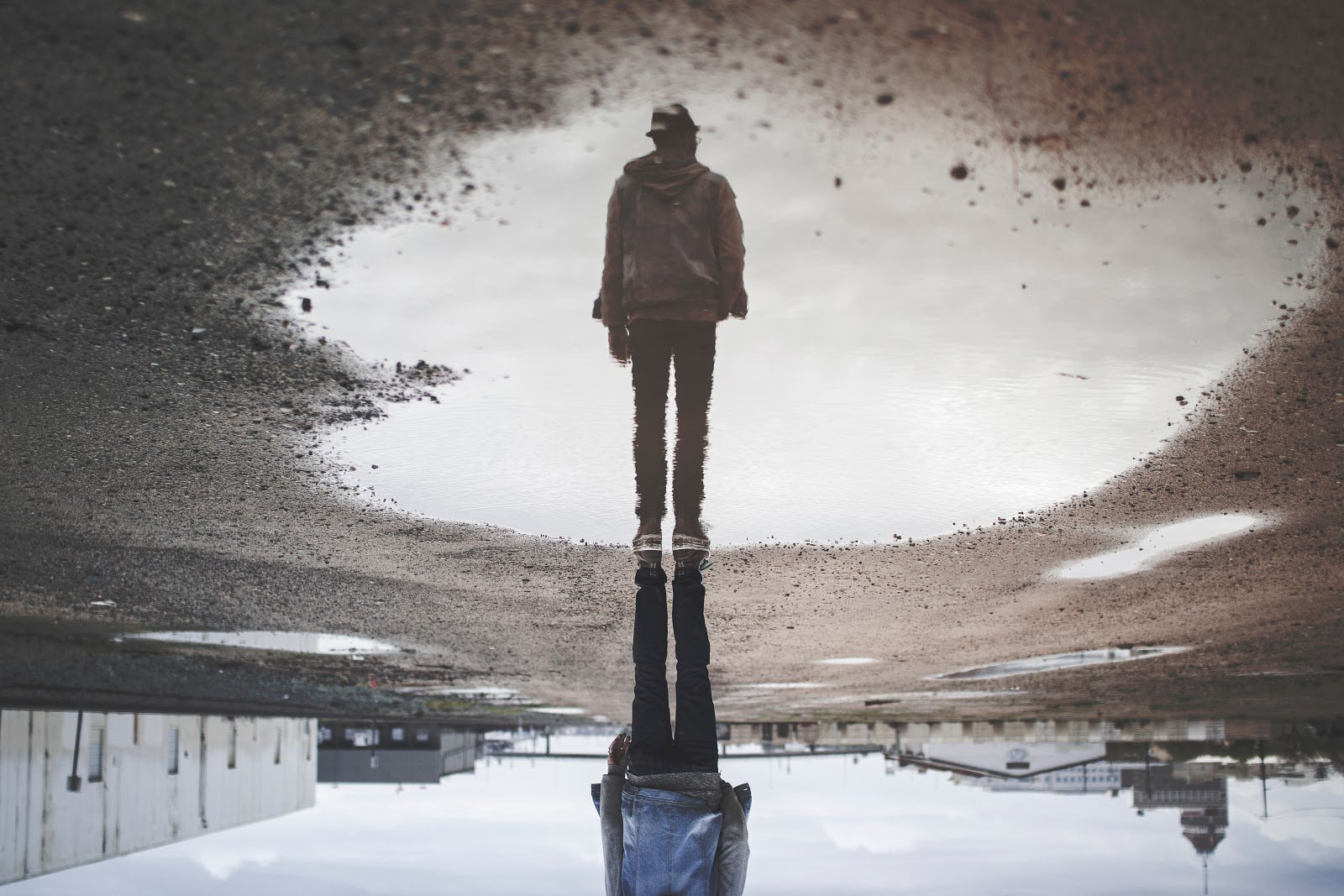 Reflection of a man standing in front of a puddle by Randy Jacob
