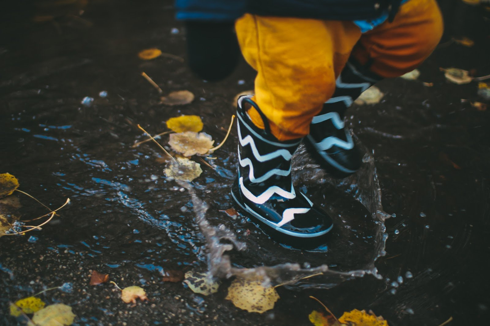 A child's legs in black and white boots skipping through a puddle by Daiga Ellaby