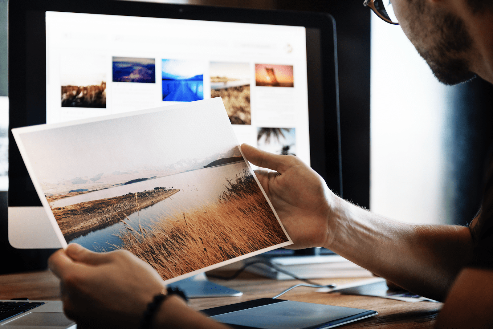 Man holding up a landscape photo at his work desk by rawpixel