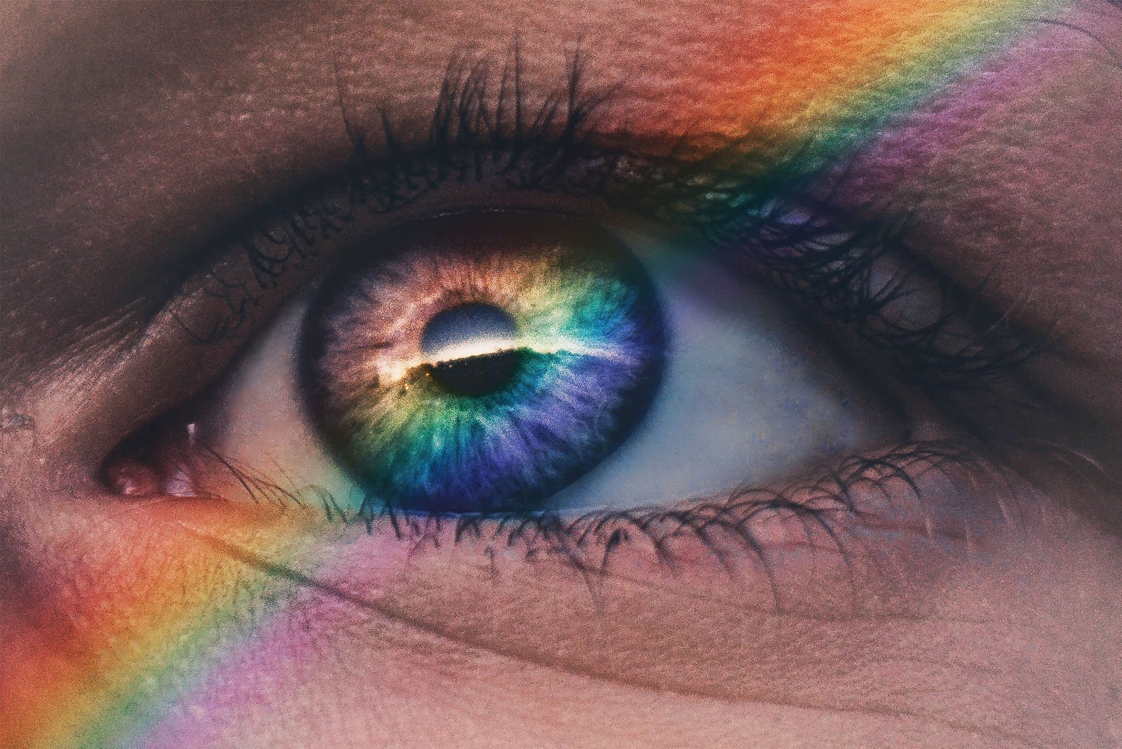 Closeup of an eye with a rainbow of light splashed across by Harry Quan
