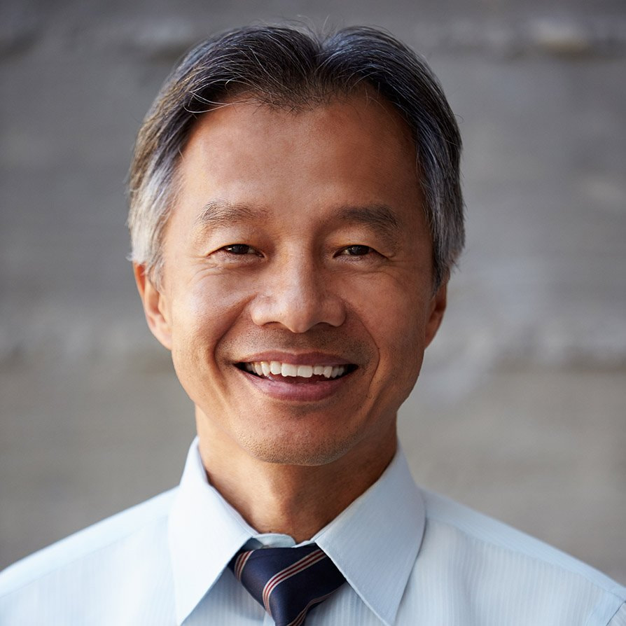 Asian Businessman Standing Against Wall In Modern Office